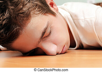Young Man Sleeping on the Table in Home inerior