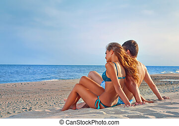 happy couple sitting on the beach