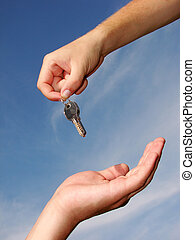 Hands with key on a background sky...