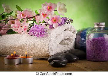 Outdoor spa massage setting  with candlelight on green background