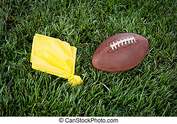 Football penalty flag - A yellow penalty flag and football...