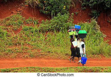 Kenyan Women Carrying Baskets of Laundry Along the Road Side