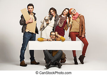 Group of friends holding advert board