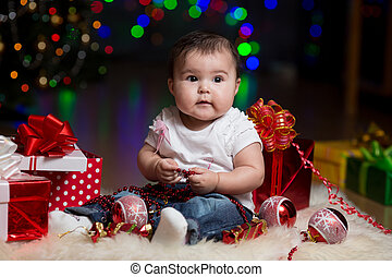 baby girl with gifts under Christmas tree