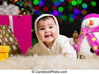 smiling baby girl near Christmas tree with gifts