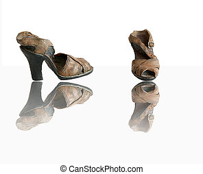 Old ceramic shoes with reflection, isolated on a white background