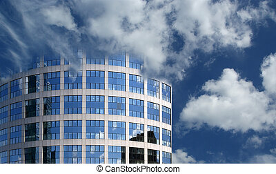 Reflection of a cloudy sky in glass wall of an office...