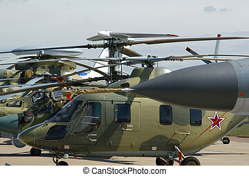 A number of modern military helicopters in the parking lot