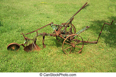 antique plow at a farm in the summer field