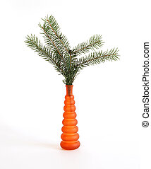 Bouquet with spruce branches in the orange glass vase on a white background