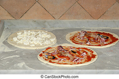 Pizza being baked in a wood fire brick oven in a restaurant