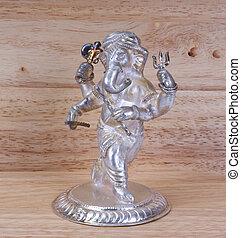 Deity Hindu god of wisdom and prosperity Ganesha on a background of wood, silver