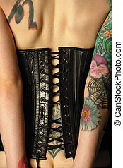 Leather corset - A young slim women with arm and back...