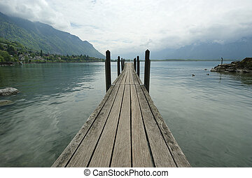 The wooden pier for boats and yachts on the background of...