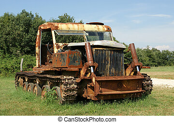 Old rusted tractor in a summer field