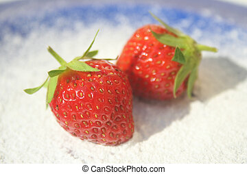 Strawberries on a blue plate - Two ripe red strawberries on...