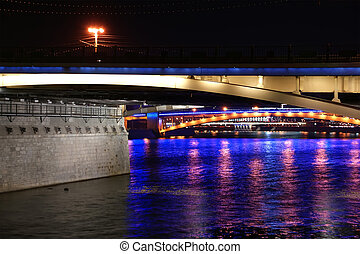 bridges on the river at night with lights reflected in water