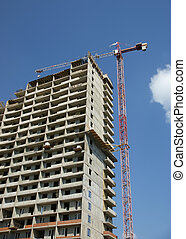 Building crane at the background of a multi-storey building under construction