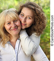 Middle age woman with her daughter outdoors