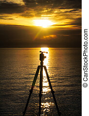 silhouette of a tripod at sunset over sea