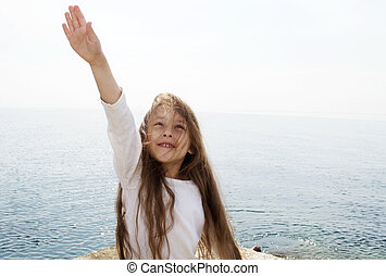 girl is pulling her hand up against the sea