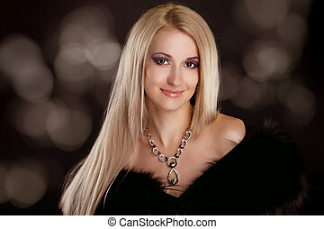 Beautiful woman with blond hair and evening make-up. Jewelry...