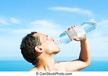 man drinking water - A young man thirsty eagerly drinking...