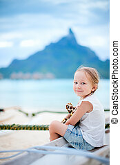 Little girl on vacation on Bora Bora island with Otemanu...
