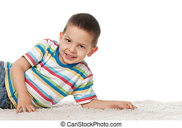 Joyful little boy on the carpet