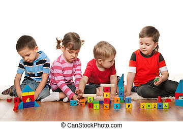 Four children are playing on the floor with blocks