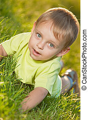 Funny little boy lying on the grass - A little boy is lying...