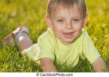 Funny little boy lying on the green grass - A smiling little...
