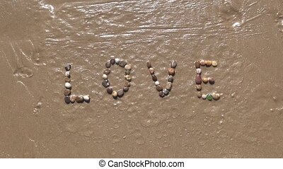 Love on sand beach - Love word writing with small stones on...