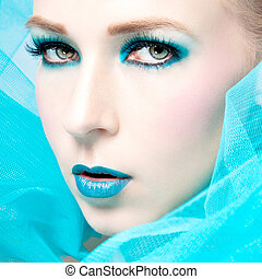 beautiful woman with extreme colorfull make up in turquoise