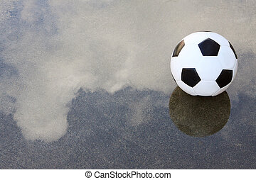 soccer football on wet ground with water reflection cloud...