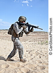 combat movement - US soldier going through the desert during...