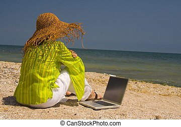Woman sitting on beach with laptop - Woman in hat sitting on...