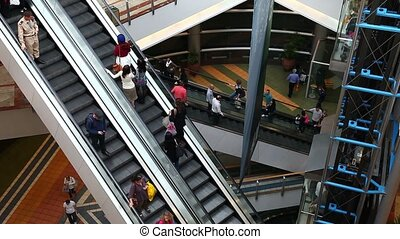 Escalator with people in the mall.