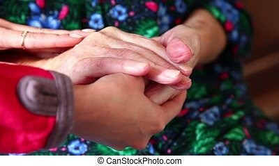 Elderly - Young hand comforting a pair of old wrinkled hands...