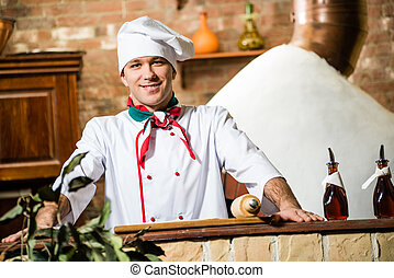 portrait of a cook, behind a stone table and looks ahead