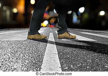 man crossing street at night - Feet of man crossing street...