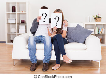 Couple with question marks - Couple in the living room with...