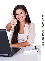 Woman sitting at laptop giving a thumbs up