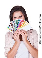 Attractive woman chooses a color scheme Studio portrait over...