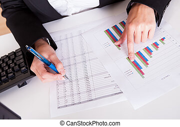Woman working with bar graphs - Overhead cropped image of...