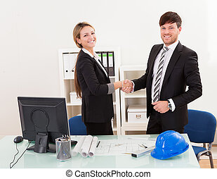Architects shaking hands in the office