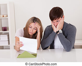 Shock portrayed on man's face after reading letter.