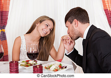 Man kissing a woman's hand at a romantic dinner as she looks...