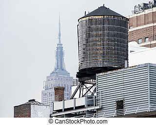 Water Tower With Empire State Building - On a hazy day in...