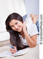 Attractive woman writing in a diary - Attractive casual...